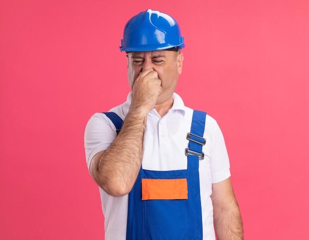 Ontevreden volwassen bouwersmens in uniform houdt neus vast die op roze muur wordt geïsoleerd