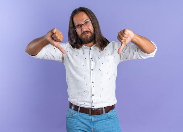 Ontevreden volwassen knappe man met een bril die naar een camera kijkt met duimen naar beneden geïsoleerd op een paarse muur
