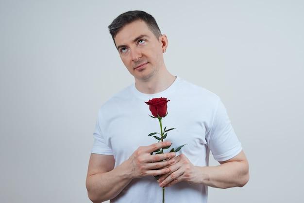 Ontevreden volwassen man in een wit t-shirt met een rode roos in zijn handen op een grijze achtergrond. fijne valentijnsdag.