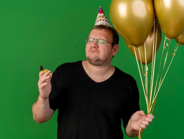 Ontevreden volwassen slavische man in optische bril met verjaardagspet houdt heliumballonnen vast en kijkt naar fluitje