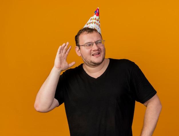 Ontevreden volwassen slavische man in optische bril met verjaardagspet staat met opgeheven hand naar de zijkant kijkend