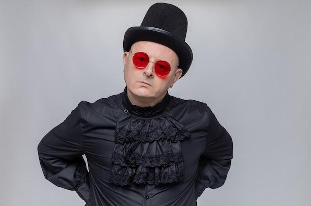 Ontevreden volwassen slavische man met hoge hoed en met zonnebril in zwart gotisch shirt op zoek