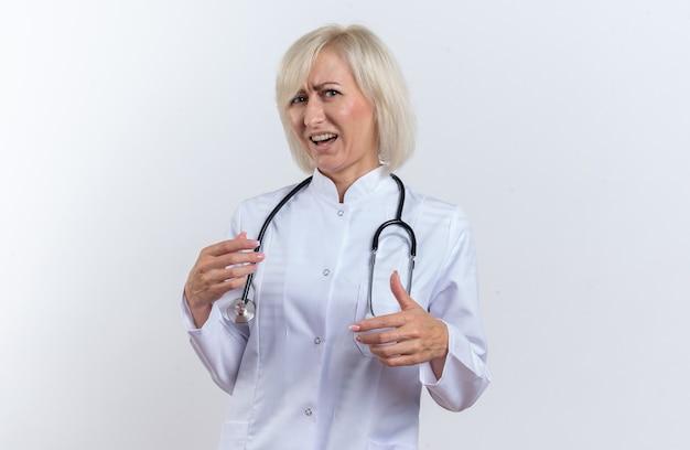 Ontevreden volwassen slavische vrouwelijke arts in medische mantel met stethoscoop kijken naar camera geïsoleerd op een witte achtergrond met kopie ruimte