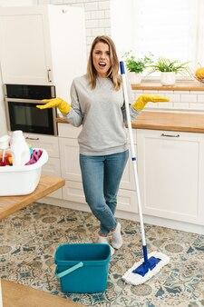 Ontevreden vrouw huisvrouw in handschoenen kwalijk tijdens het dweilen van de vloer in de moderne keuken