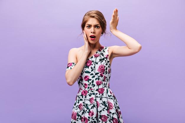 Ontevreden vrouw in jurk vormt op paarse achtergrond. ontevreden jong meisje dat in heldere uitrusting camera op geïsoleerde achtergrond onderzoekt.