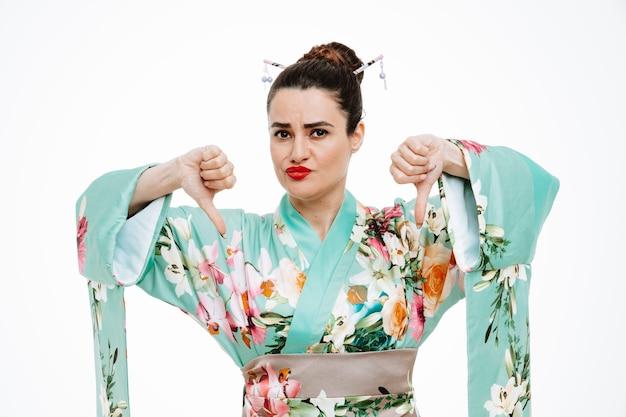 Ontevreden vrouw in traditionele japanse kimono die ontevreden is met duimen naar beneden op wit