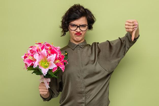 Ontevreden vrouw met kort haar die een boeket bloemen vasthoudt en duimen naar beneden laat zien