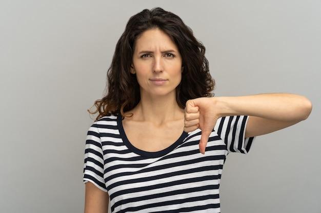 Ontevreden vrouw met wantrouwend gezicht met duim omlaag, kijk niet graag naar camera in studio.