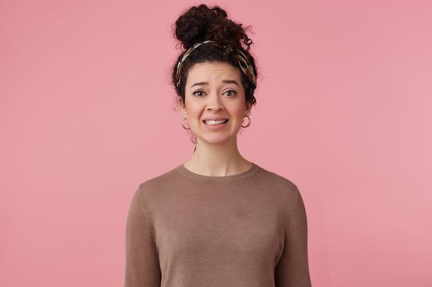 Ontevreden vrouw, onzeker meisje met donker krullend haarknotje. met hoofdband, oorbellen en bruine trui. heeft make-up. emotie concept