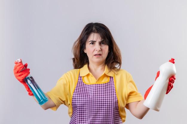 Ontevreden vrouw van middelbare leeftijd die schort en rubberhandschoenen draagt die schoonmakende levering houden