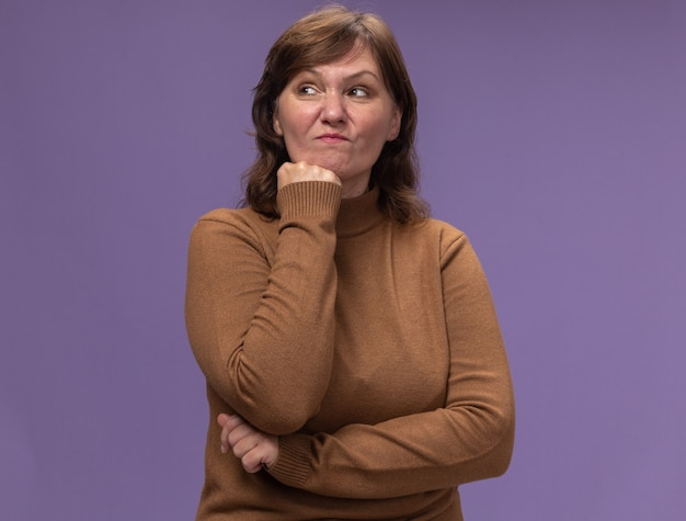 Ontevreden vrouw van middelbare leeftijd in bruine coltrui opzij kijken met hand op haar kin denken staande over paarse muur