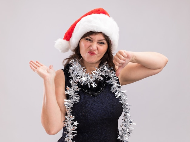 Ontevreden vrouw van middelbare leeftijd met een kerstmuts en een klatergoudslinger om de nek die naar een camera kijkt met een lege hand en een duim omlaag geïsoleerd op een witte achtergrond