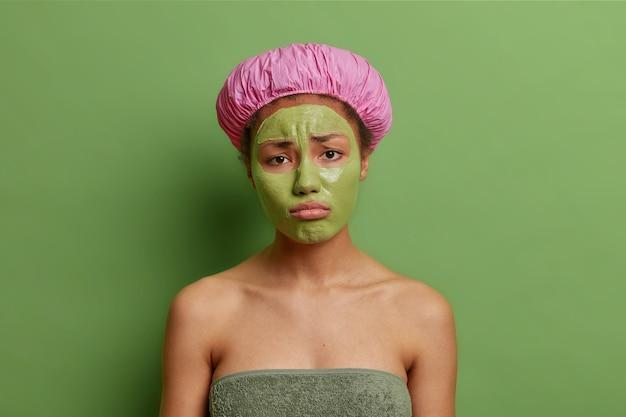 Ontevreden vrouwelijk model kijkt droevig naar camera past reinigingsmasker toe op gezicht pruiltjes lippen draagt badmuts zachte handdoek rond naakte lichaam geïsoleerd over groene muur
