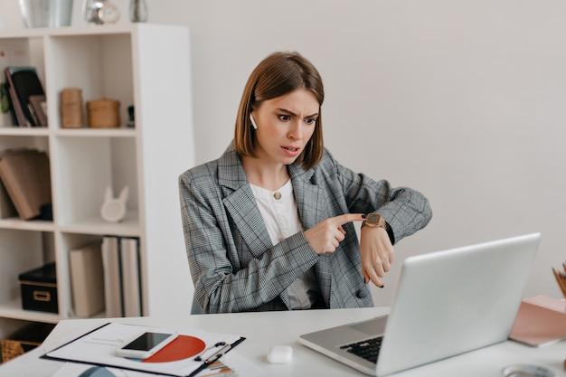 Ontevreden vrouwelijke baas praat op video en laat haar horloge zien, wat haar ondergeschikten herinnert aan de deadline.