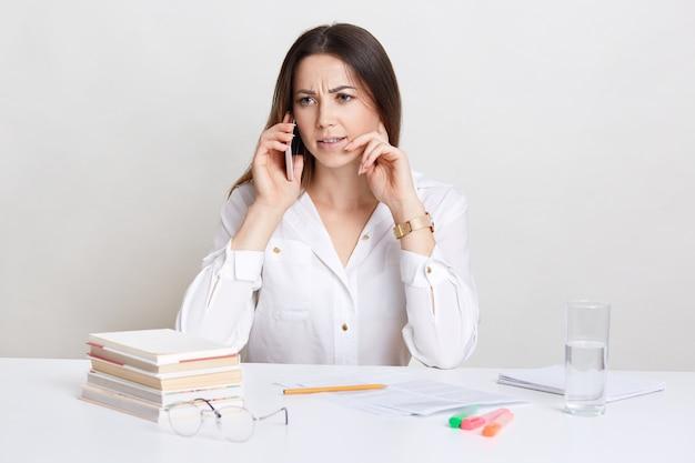 Ontevreden vrouwelijke professor praat op mobiele telefoon, draagt wit overhemd, bespreekt iets met verontwaardigde uitdrukking, heeft bril, stapel boeken, glas water op bureau. mensen, zaken, carrière