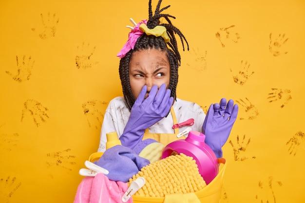 Ontevreden vuile afro-amerikaanse vrouw poseert in rommelige kamer bedekt neus ruikt iets stinkends en walgelijks houdt adem in staat in de buurt van wasmand geïsoleerd over gele muur