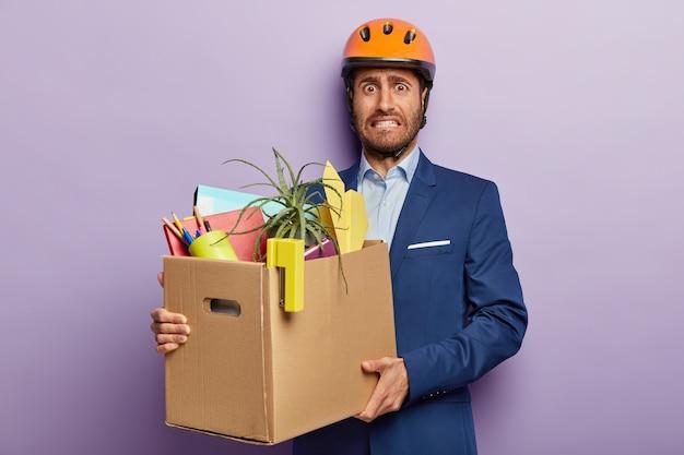 Ontevreden zakenman poseren in stijlvol pak en rode helm op kantoor