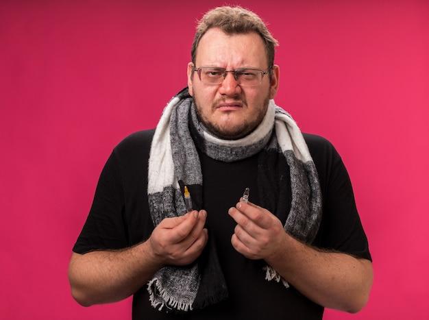 Ontevreden zieke man van middelbare leeftijd met een sjaal die een spuit vasthoudt met een ampul geïsoleerd op een roze muur