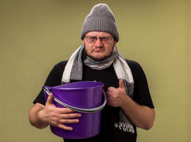 Ontevreden zieke man van middelbare leeftijd met een wintermuts en sjaal met een plastic emmer die duim omhoog laat zien