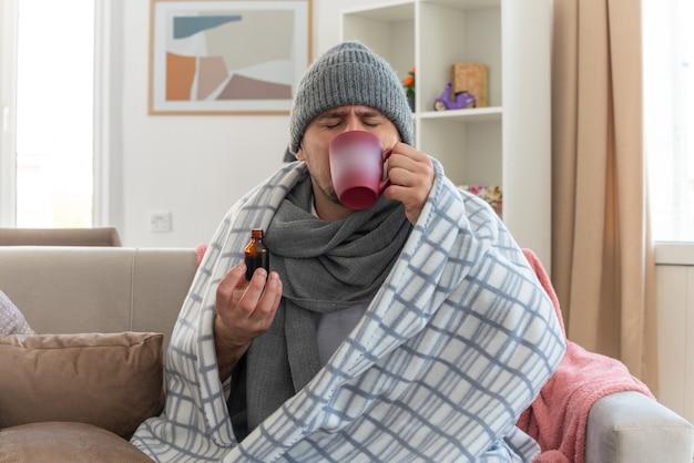 Ontevreden zieke slavische man met sjaal om nek met wintermuts gewikkeld in geruite medicijnen drinken uit beker zittend op de bank in de woonkamer