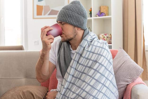 Ontevreden zieke slavische man met sjaal om nek met wintermuts gewikkeld in plaid drinken uit beker zittend op de bank in de woonkamer