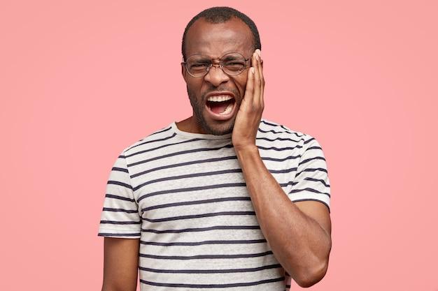 Ontevreden zwarte man fronst zijn wenkbrauwen, heeft een negatieve gezichtsuitdrukking, voelt walging tegen iets