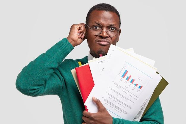 Ontevreden zwarte man stelt boekhoudkundig rapport op, houdt papieren met inforgrafische vast, draagt een bril voor een goed zicht
