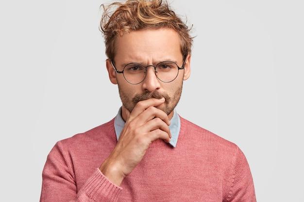 Ontevredenheid droevige europese mannelijke ondernemer met nors gelaatsuitdrukking, fronst gezicht van ontevredenheid, kijkt verbaasd, houdt de hand op de mond, draagt vrijetijdskleding, staat voor financiële crisis, heeft veel schulden