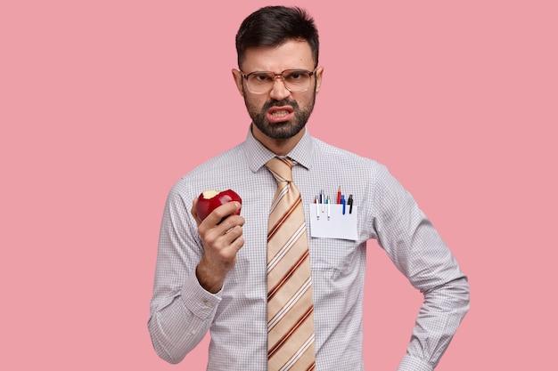 Ontevredenheid geërgerd bebaarde man fronst zijn wenkbrauwen, klemt zijn tanden op elkaar van woede, eet sappige appel, houdt niet van iemands idee, gekleed in formele kleding