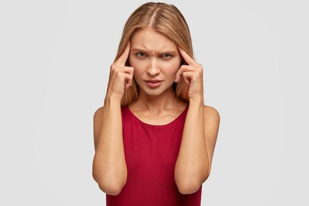 Ontevredenheid mooie jonge vrouw fronst gezicht en houdt haar wijsvingers op slapen, onthoudt noodzakelijke informatie