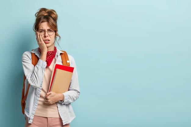 Ontevredenheid ongelukkige student zakt voor examen, boos om een slecht cijfer te krijgen, houdt de hand op de wang, houdt blocnotes vast