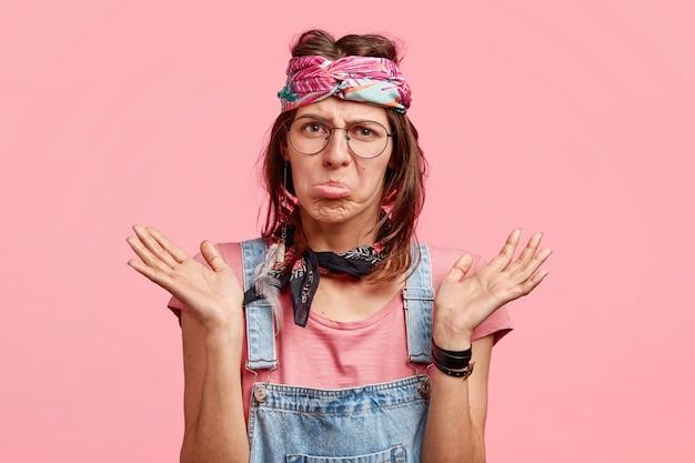 Ontevredenheid verbaasd aarzelend hippie-vrouw gebaart twijfelachtig, tuit lippen, fronst gezicht met ongelukkige uitdrukking