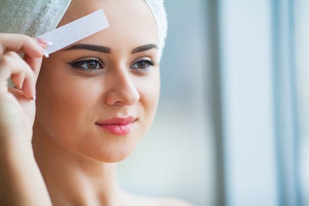 Ontharing wax. jonge vrouw die epilatie van het gezicht ontvangt