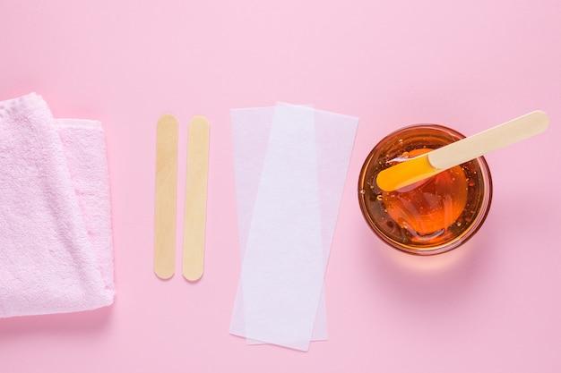 Ontharingssuikerpasta met een houten spatelhanddoek en ontharingsstrips op een roze achtergrond