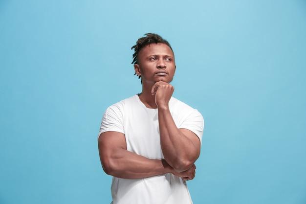 Onthoud alles. laat me denken. twijfel concept. twijfelachtige, bedachtzame afro-amerikaanse man die zich iets herinnert. jonge emotionele man. menselijke emoties, gezichtsuitdrukking concept. studio. geïsoleerd op trendy blauw