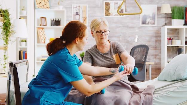 Onthullend schot van vrouwelijke verpleegster die een oudere vrouw helpt haar spieren te herstellen na een ongeval. ze ligt in een ziekenhuisbed in een bejaardentehuis