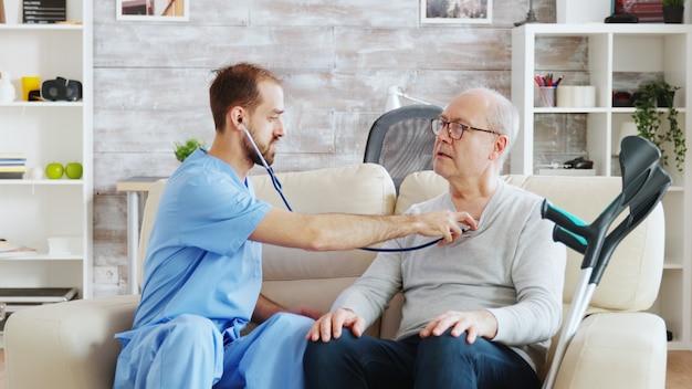 Onthullende opname van een jonge verpleger die luistert naar de hartslag van een oude gepensioneerde man in een licht en gezellig verpleeghuis. verzorger en maatschappelijk werker