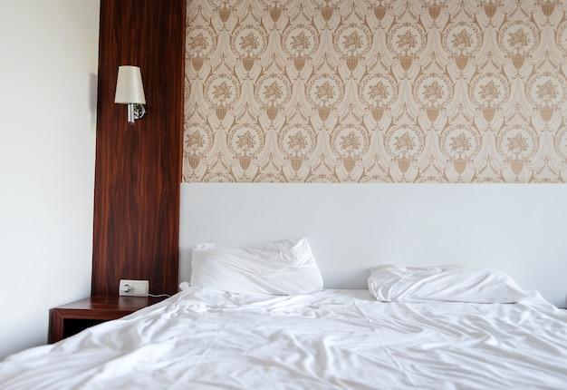 Ontmanteld een bed in een hotel met witte lakens.
