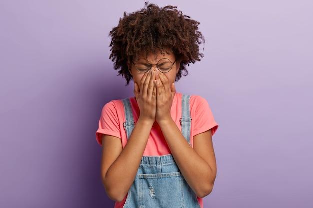 Ontmoedigde wanhopige vrouw bedekt gezicht, jankt van negatief nieuws, heeft een droevige gezichtsuitdrukking, draagt een ronde bril