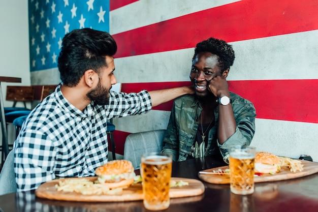Ontmoet na het werk. twee lachende jongens die plezier hebben terwijl ze tijd doorbrengen met vrienden in een pub en bier drinken met hamburgers.