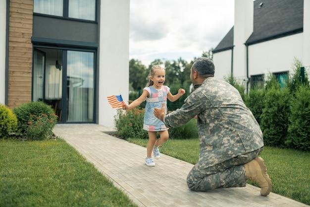 Ontmoeting dochter. militaire dienaar ontmoet zijn schattige mooie meisje in de buurt van het huis terwijl hij terug naar huis komt