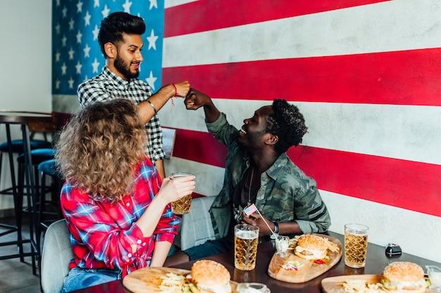 Ontmoeting in de kroeg. vrienden die hamburgers eten, leuke tijd hebben en bier drinken, samen tijd doorbrengen