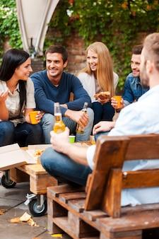 Ontmoeting met de beste vrienden. groep vrolijke jonge mensen die met elkaar praten en pizza eten terwijl ze buiten zitten