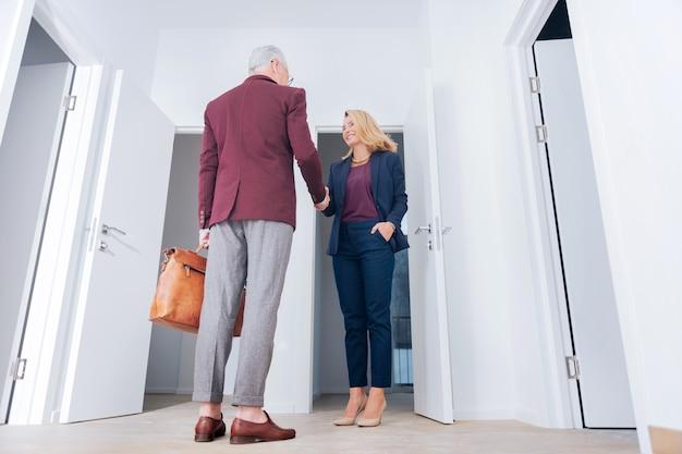 Ontmoeting met de klant. blondharige aantrekkelijke aangename makelaar ontmoet haar klant voor de deur van een luxe appartement