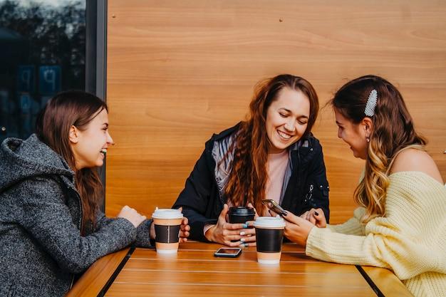 Ontmoeting van drie vriendinnen in een café in de herfst