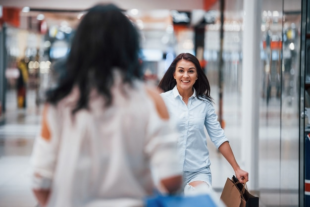 Ontmoeting van twee vriendinnen in het winkelcentrum tijdens weekendwinkeltijd.