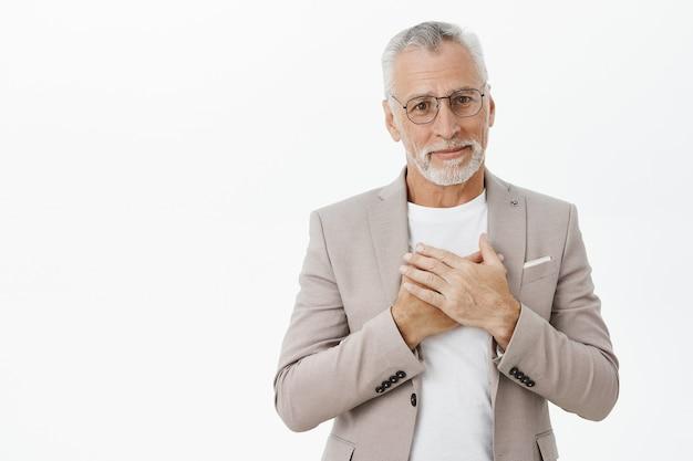 Ontroerd en tevreden glimlachende senior man die opgetogen of dankbaar kijkt