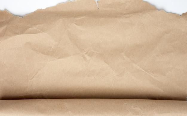 Ontrolde het bruine verpakkingspapier dat op witte ruimte wordt geïsoleerd