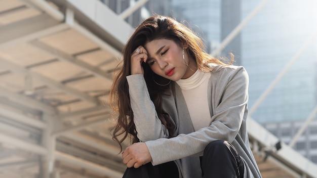 Ontslaan. ontslagen. ontslagen zakenvrouw zittend op trappen van kantoorgebouw buiten. depressieve werkloosheid bij jonge zakenvrouwen als gevolg van de coronaviruscrisis. zorgen geen baan geen geld. ontslagen werd ontslagen.