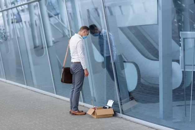 Ontslag wegens een coronavirusepidemie. ontslagen werknemer sper tegen de muur van het kantoorhoofd.